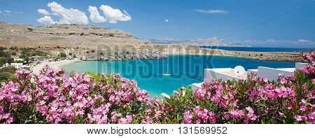 Rhodes. View of Lindos main bay with yacht, pink flowers, azure water and white houses