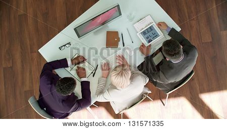 Three business people looking at monitor