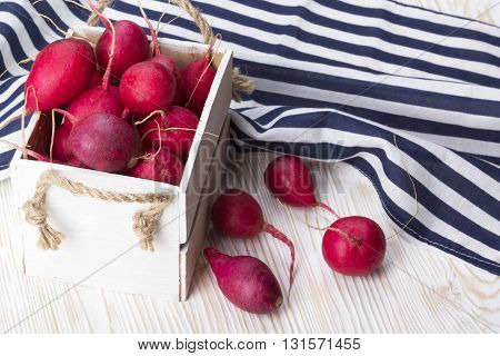 Red radishes in a wooden box on wooden desk