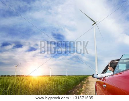 Girl in red car in a field with wind turbines at sunset.