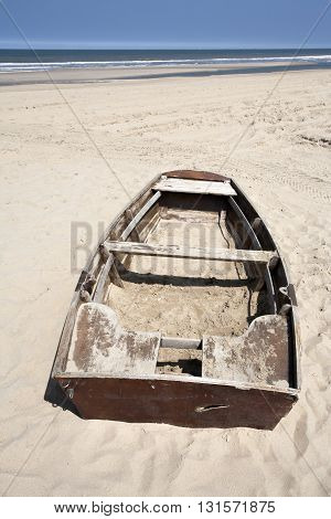 Abandoned rowing boat on the beach in the Netherlands