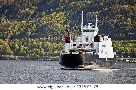 SOGNEFJORD, NORWAY - MAY 12, 2012: Gas powered ferry Sogn of Fjord1 shipping company moves passengers across Sognefjord