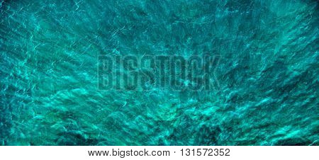 Turquoise water with shadows and glare. Background or texture
