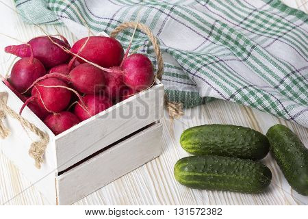 Cucumbers and red radishes in a wooden box on wooden desk