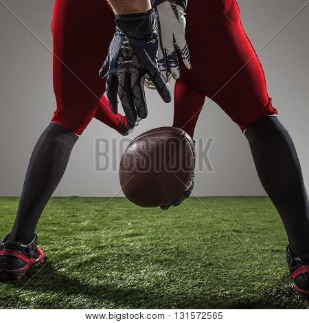 The american football player in action on green grass and gray background.