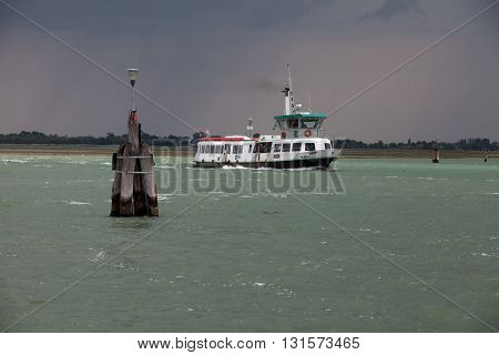 VENICE, ITALY - JUNE 28, 2013: A ship transporting passengers between the Islands of Venice in inclement weather