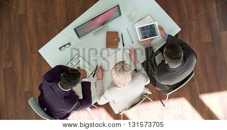 Three executives looking at diagram on touchpad and sharing their ideas