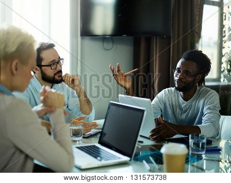 Creative manager talking to his workers at meeting