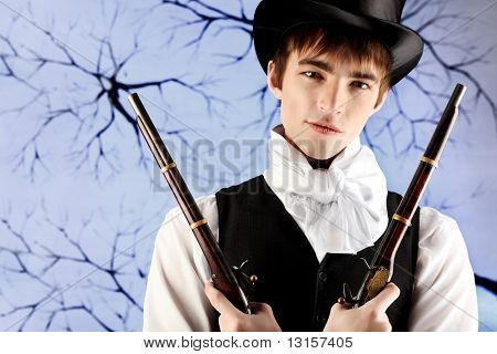 Portrait of a young gentlemen in a jacket and  top hat holding guns in his hands. Shot in a studio.