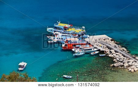 RHODES, GREECE - MAY 13, 2015: Touristic boats at the pier in the Lindos
