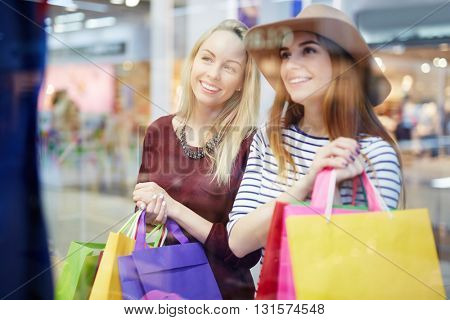 Portrait of women friends with shopping bags indoors