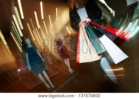 Blurred motion of woman with shopping bags