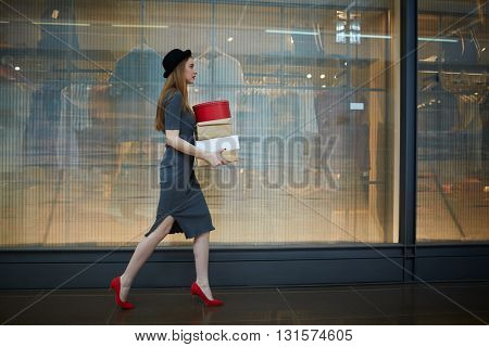 Woman walking in the mall with boxes