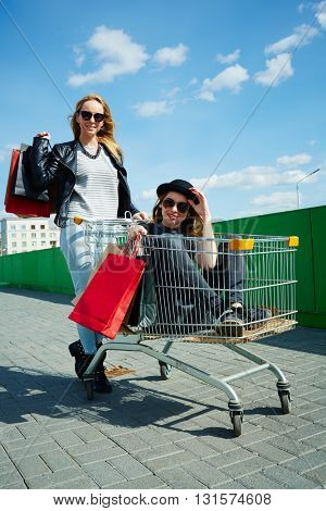 Female friends having fun with with trolley cart outdoors