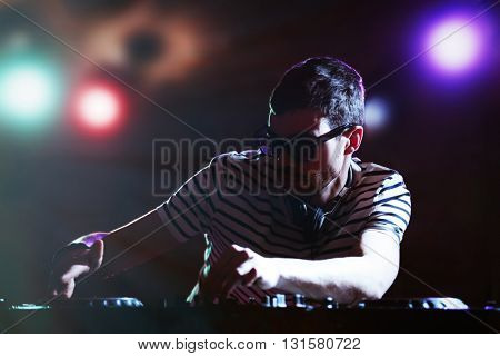 DJ playing music at mixer on colorful blurred background