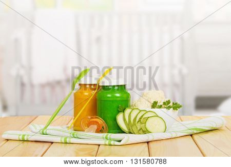ars of baby puree vegetables: cauliflower, zucchini, towels, spoons and bimbo on a background of light wood.