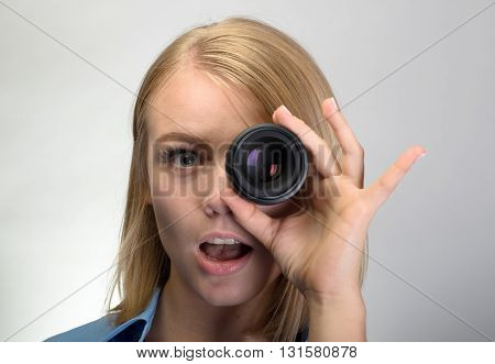 Young Funny Woman Using Camera Lens Over Gray Background
