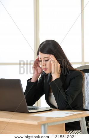 Tired asia businesswoman with headache at desk in the office