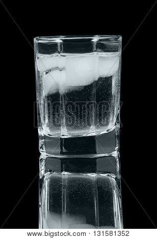 A glass of vodka with ice isolated on a black background.