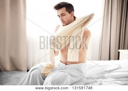 Young man waking up in bed and dressing up.