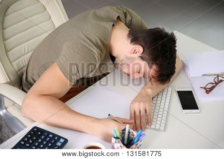 Young man sleeping at the working place.