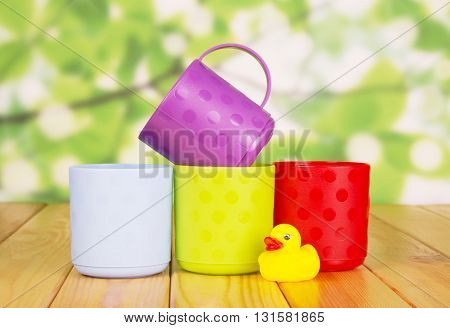Colorful plastic cups and rubber duck on a green abstract background.