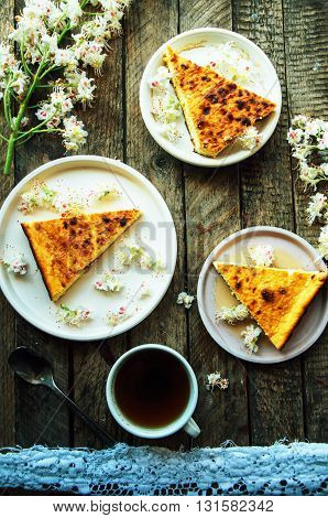 Sweet casserole with cottage cheese and raisins on the table. Cheese casserole with raisins on plate on napkin on wooden table close-up