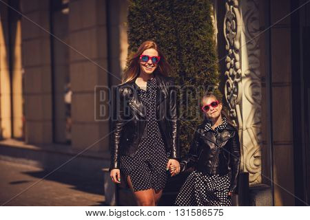 cool mom and daughter in city. fashion clothes