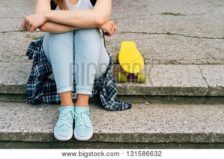 Young Woaman In Jeans, Sneakers And T-shirt Sitting On The Steps Next To Her Yellow Skateboard Outdo