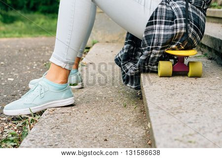 Girl Sitting On A Skateboard In The Park