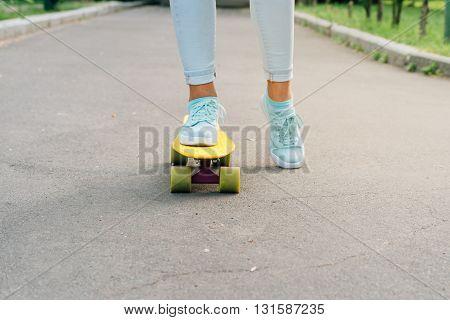 Female Feet In Sneakers Riding A Skateboard On Asphalt