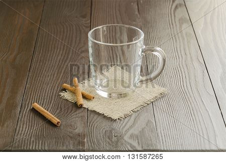 Empty glass cup on a linen napkin with cinnamon sticks.
