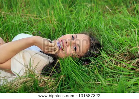 Young beautiful girl lying on the grass and looking at camera.