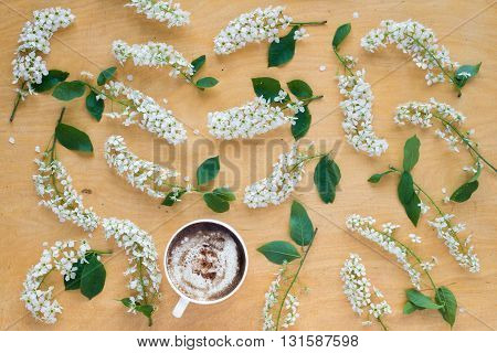 Coffee and twigs of blooming bird cherry on wooden board.