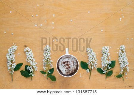 Coffee and twigs of blooming bird cherry laying out in a row on wooden board.