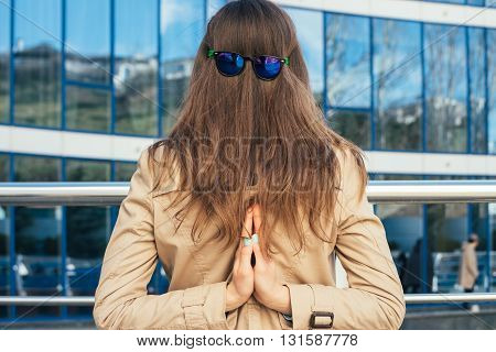 Woman in beige coat with sun glasses at the nape view from the back