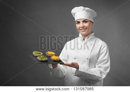 Professional chef holding  fruit tarts on grey background.