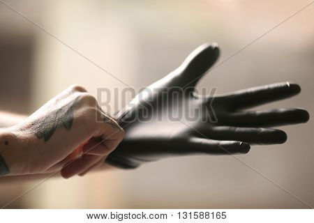 Man with tattoo wearing black latex gloves on blurred background