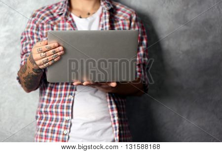 Young man with tattoo holding laptop on grey background