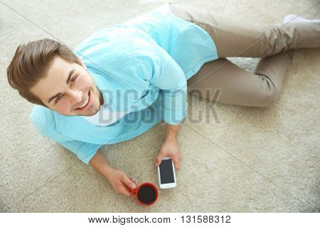 Handsome man in blue shirt with smart phone and cup of coffee on the floor