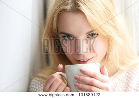 Blonde beautiful  girl sitting by the window with cup of tea or coffee in her hands