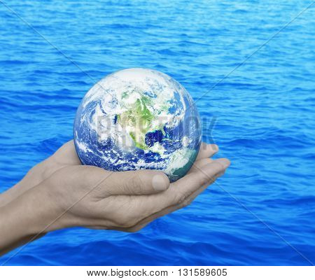 Earth in hands over blue sea background Environment concept Elements of this image furnished by NASA