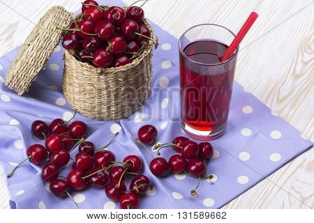 Cherry basket and juice on the white wooden desk