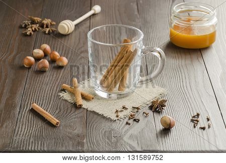Glass cup with cinnamon sticks on a linen napkin with honey nuts and spice . Focus is on the cinnamon sticks