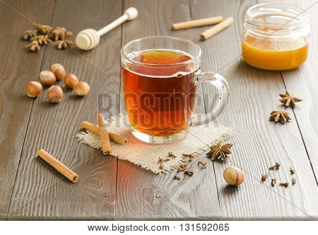Glass cup of tea on a linen napkin with cinnamon sticks honey nuts and spice.