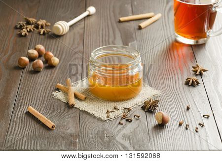 Jar of honey on a linen napkin with cinnamon sticks nuts and spice