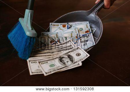 Man rakes in the money in savok. Sweep of the banknote in the trash. Clean money in the trash