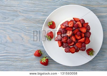 Tart with strawberries, raspberries and cream on blue wooden background. Top view.
