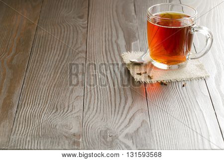 Glass cup of tea with clove on a wooden background