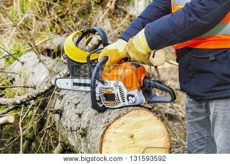 Lumberjack trying to start chainsaw in forest .